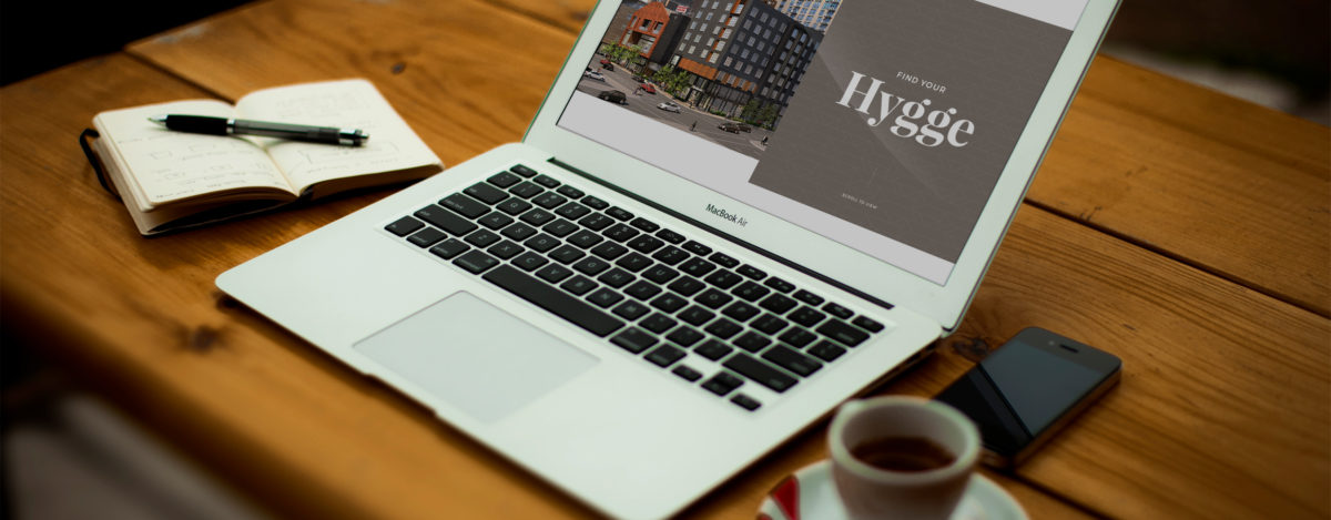 The website of the Elliot Park Hotel on a MacBook, sitting on a wooden desk next to a cup of coffee.